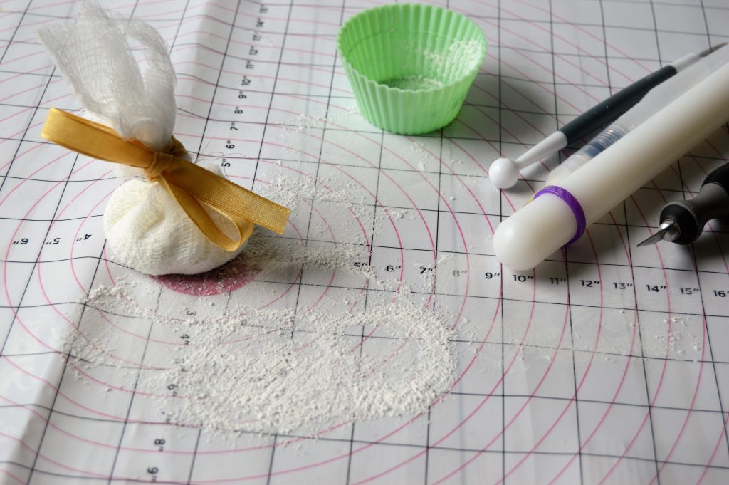 Using a DIY made cornstarch puff makes fondant not stick when decorating cakes with fondant