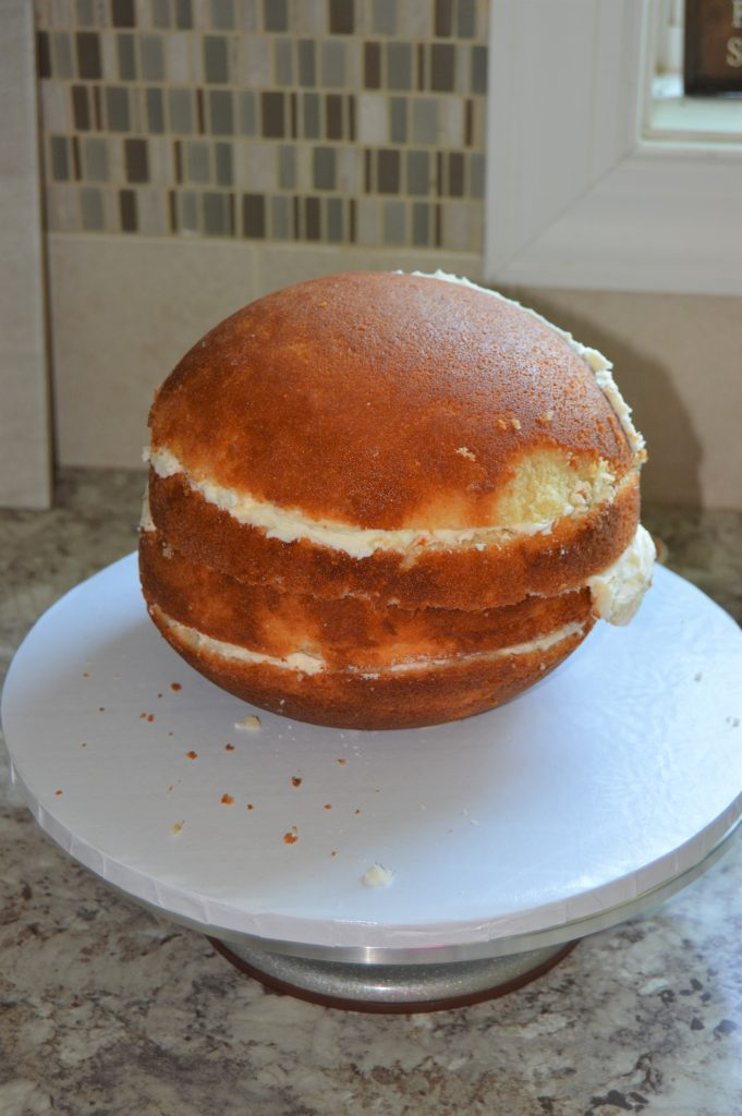 Stacking and filling a sphere cake.