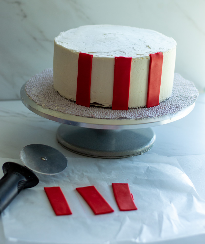 buttercream cake with red strips of fondant