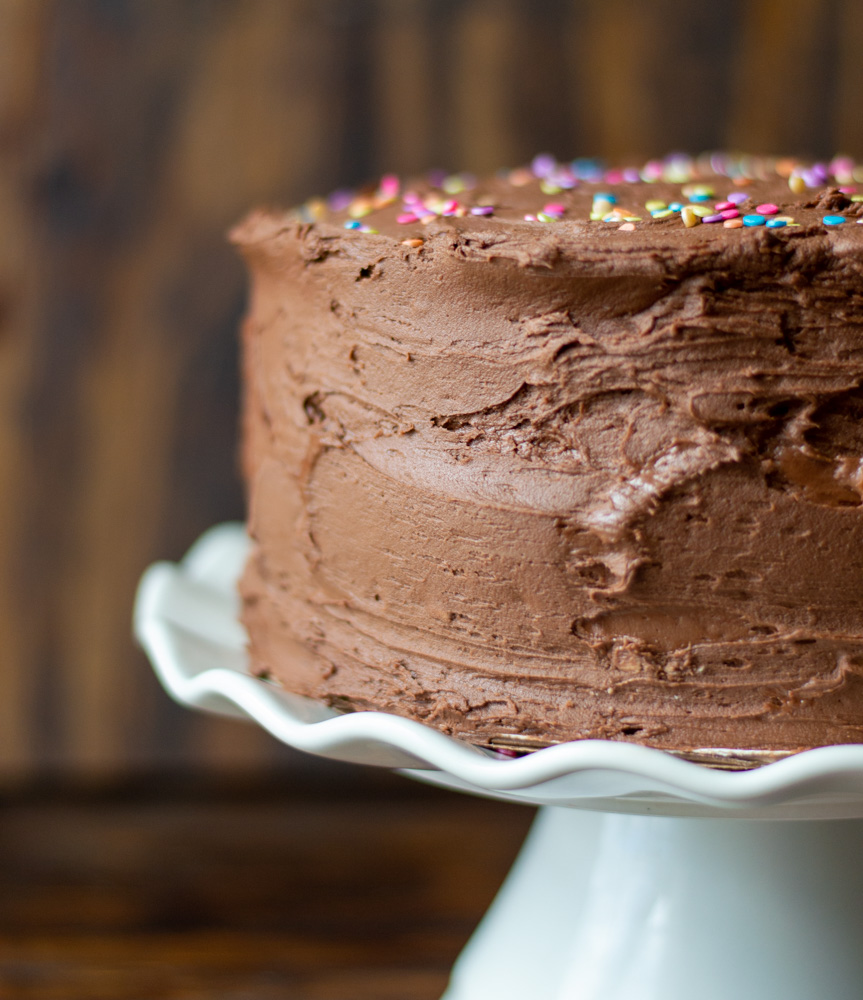 chocolate frosted cake on cake stand